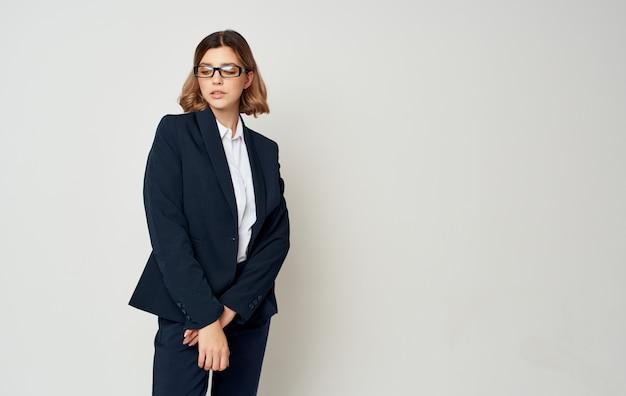 Geschäftsfrau in einer blauen jacke und in der hose auf einem licht, das mit modell beschnitten wird