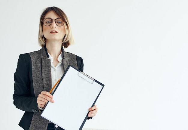 Geschäftsfrau in einer jackenmanager-modellbrille und einem weißen blatt papier