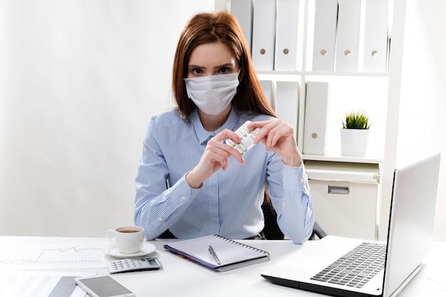 Geschäftsfrau in einer maske am arbeitsplatz hält eine tablette in den händen