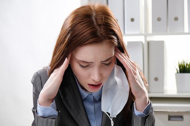 Geschäftsfrau in einer medizinischen schutzmaske arbeitet im büro