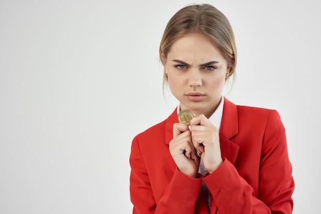 Geschäftsfrau in einer roten jacke goldmünze bitcoin hellen hintergrund. foto in hoher qualität