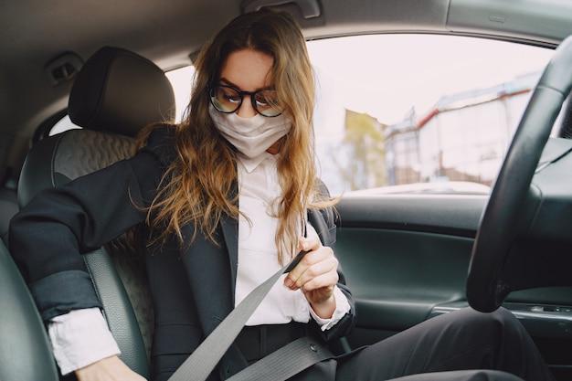 Geschäftsfrau in einer schwarzen maske, die in einem auto sitzt