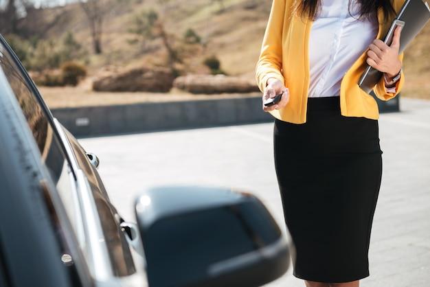 Geschäftsfrau in gelber jacke, die die tür ihres autos schließt