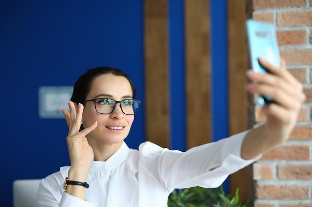 Geschäftsfrau in gläsern winkt und spricht auf videoanruf
