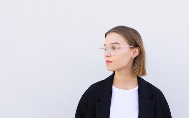 Geschäftsfrau in jacke und brille schaut auf die copyspace-seite, isoliert auf weiß