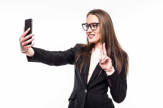 Geschäftsfrau in klassischer schwarzer suite auf weiß hat einen videoanruf auf ihrem handy