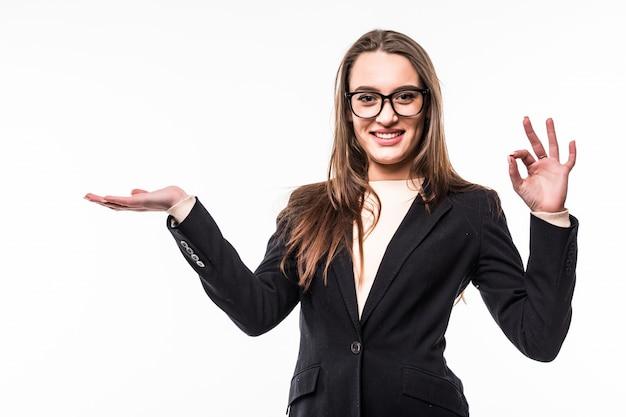 Geschäftsfrau in klassischer schwarzer suite auf weiß zeigt etwas mit der hand