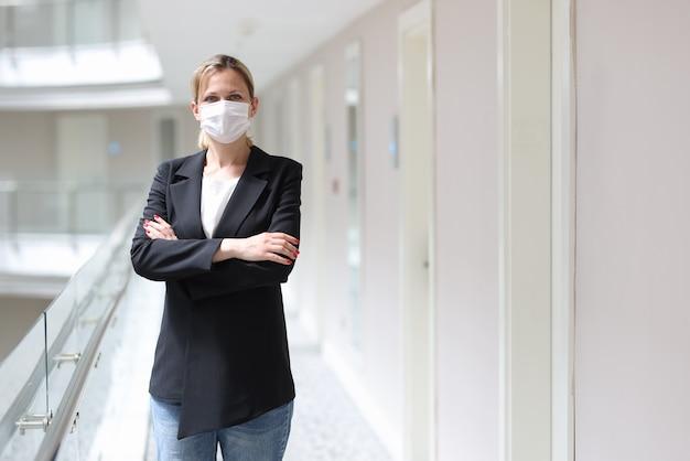 Geschäftsfrau in medizinischer schutzmaske steht mit verschränkten armen im hotelflur