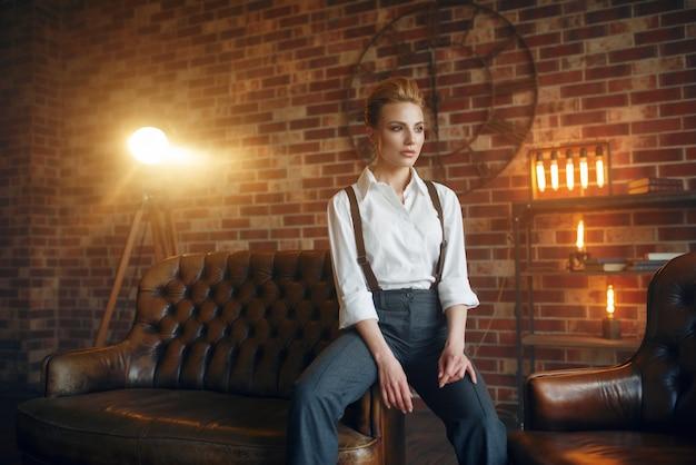 Geschäftsfrau in strengen kleidern auf ledercouch