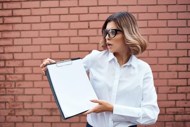 Geschäftsfrau in weißem hemd und brille mit dokumenten auf der straßenmauer. foto in hoher qualität