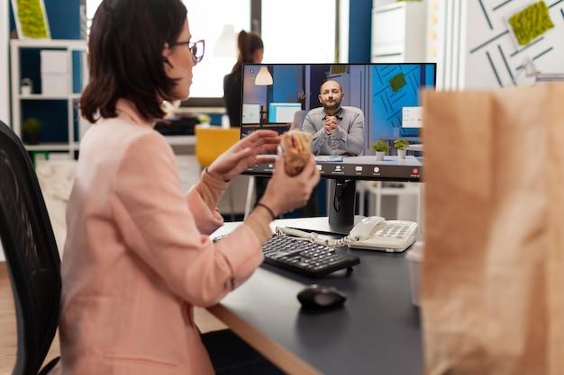 Geschäftsfrau isst liefer-sandwich zum mitnehmen während einer online-videokonferenz-konferenz, die mit einem remote-mitarbeiter diskutiert?