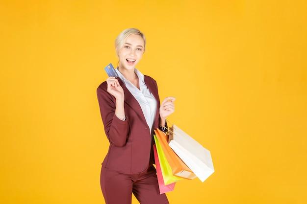 Geschäftsfrau ist mit dem einkauf im studiogelbhintergrund glücklich