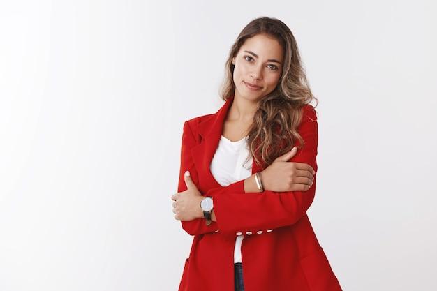 Geschäftsfrau kann zart aussehen. studio schoss attraktive weibliche junge berufstätige frau mit roter jacke, die sich selbst lächelnd umarmte, süßer, geneigter kopf, der weich anstarrte, weibliche angestellte, die an einer büroparty teilnahmen