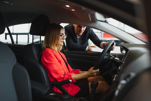 Geschäftsfrau kauft ein auto bei einem autohaus.