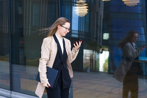 Geschäftsfrau kaukasischer abstammung in einem mantel und einem anzug mit brille schreibt sms-nachrichten auf dem p...