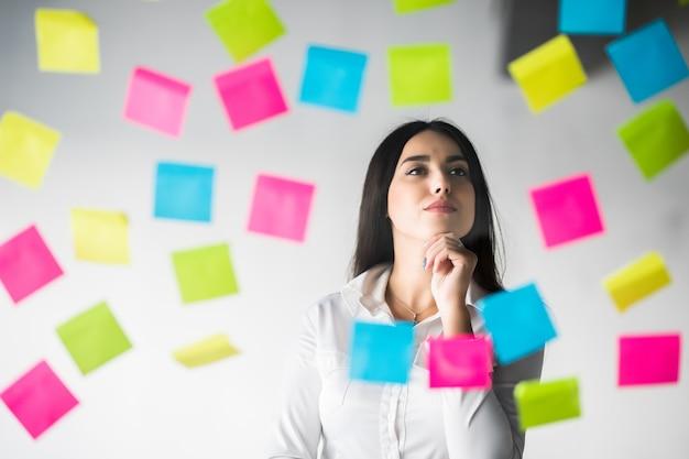 Geschäftsfrau klebt aufkleber und denkt über das projekt nach. frau, die über aufkleber nachdenkend plant.