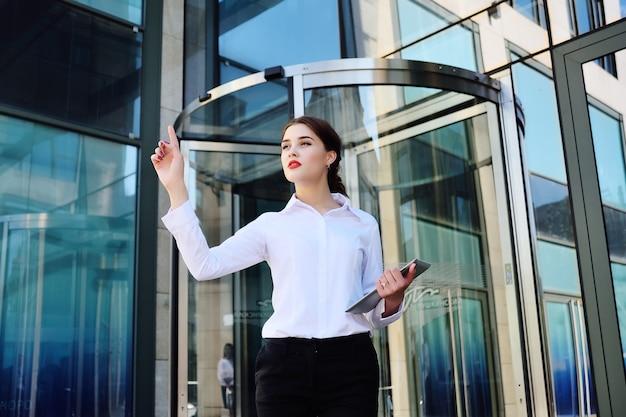 Geschäftsfrau klickt mit einem zeigefinger auf einen virtuellen bildschirm auf dem hintergrund eines bürogebäudes