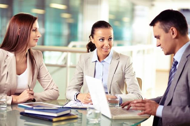Geschäftsfrau lächelnd und ihre kollegen arbeiten