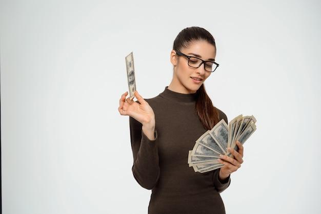 Geschäftsfrau lächelt erfreut über geld