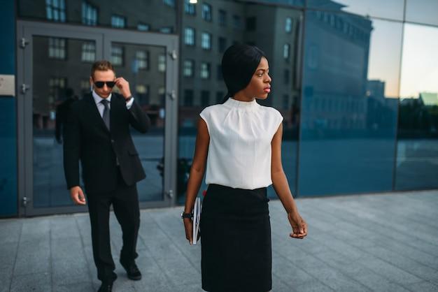 Geschäftsfrau, leibwächter im anzug