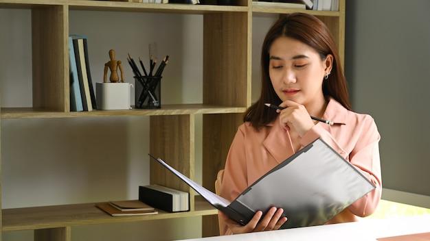 Geschäftsfrau liest geschäftsbericht im büro.