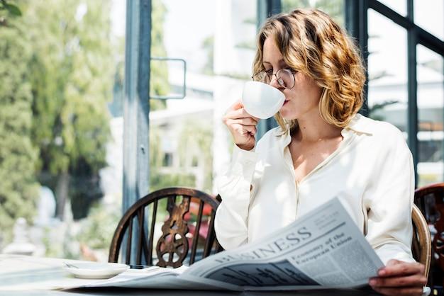Geschäftsfrau liest zeitung morgens