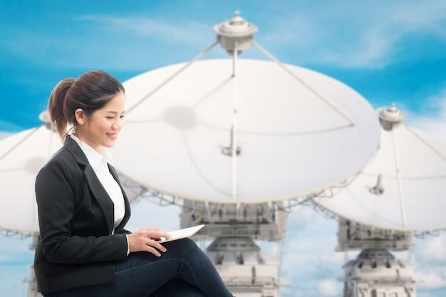 Geschäftsfrau mit 3d-rendering-satellitenschüssel-hintergrund