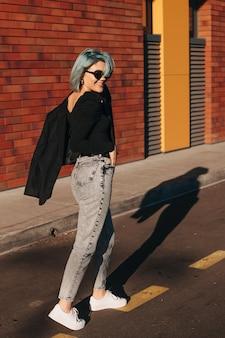 Geschäftsfrau mit blauen haaren geht auf ziegelsteinhintergrund corporate style online-lifestyle-online-banking