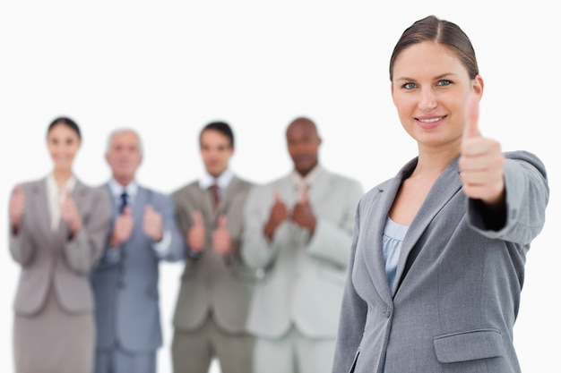 Geschäftsfrau mit dem daumen hoch und kollegen hinter ihr