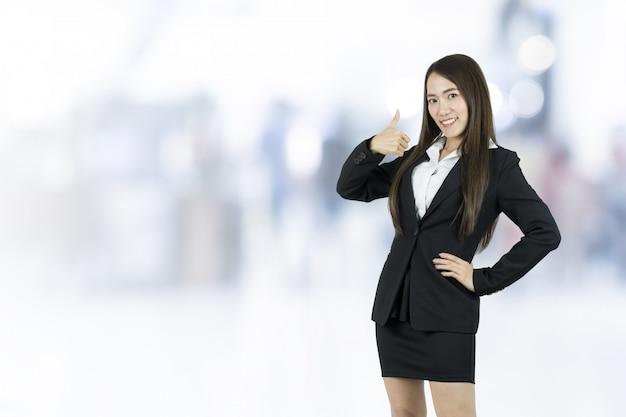 Geschäftsfrau mit dem daumen oben auf unscharfem hintergrund.