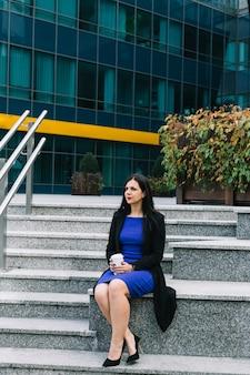 Geschäftsfrau mit dem entsorgungscup, der auf treppenhaus sitzt