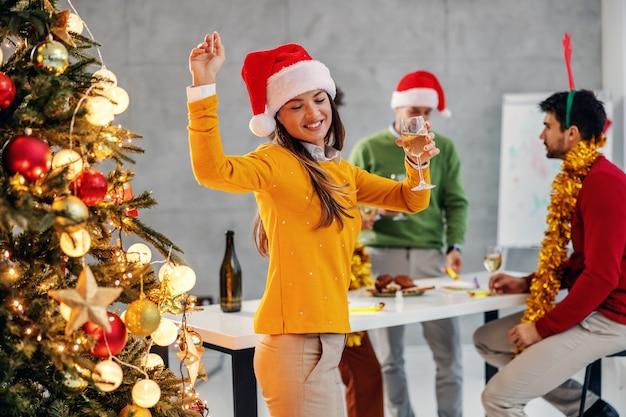 Geschäftsfrau mit dem hut des weihnachtsmanns, der champagner hält, der neben weihnachtsbaum in ihrer firma tanzt.