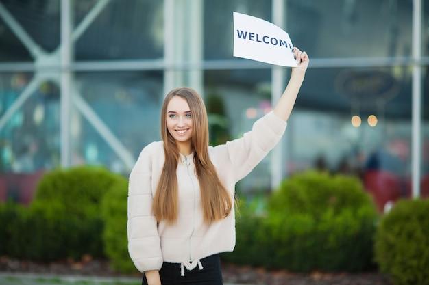 Geschäftsfrau mit dem langen haar, das ein zeichen brett mit einem willkommen hält, hat flughafen