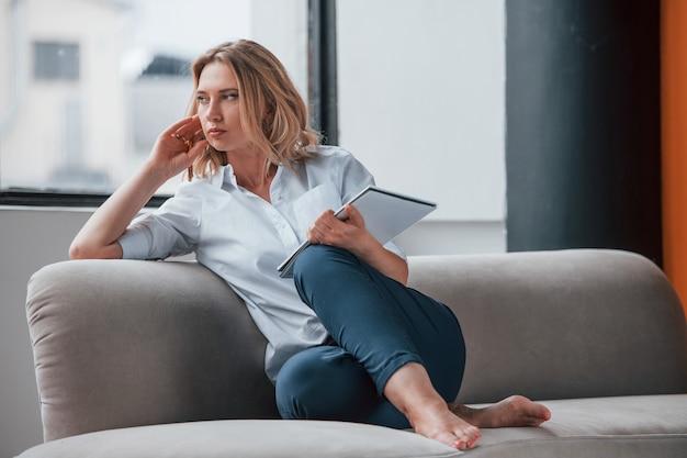 Geschäftsfrau mit dem lockigen blonden haar, das im raum gegen fenster sitzt.