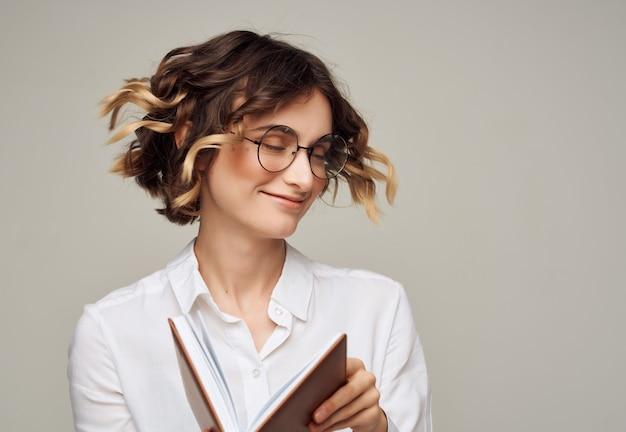 Geschäftsfrau mit dem lockigen haar mit brille professionelles executive-buch