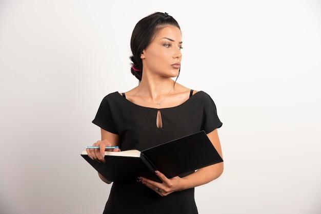 Geschäftsfrau mit dem notizbuch, das auf weißer wand aufwirft.