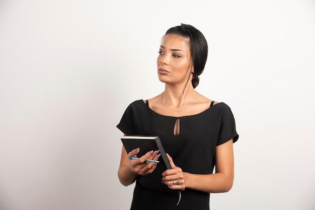 Geschäftsfrau mit dem notizbuch, das ihre seite betrachtet.