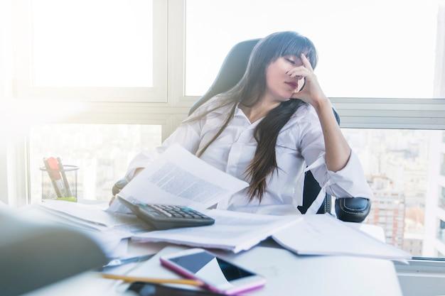 Geschäftsfrau mit dem unordentlichen schreibtisch, der im büro schläft