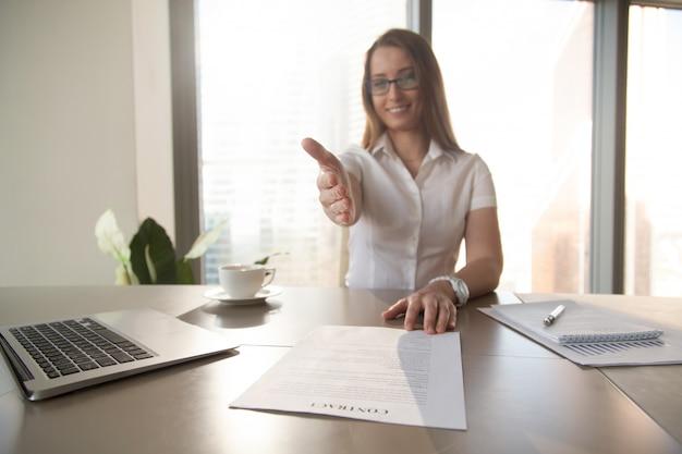 Geschäftsfrau mit dem vertrag, der ihre hand heraus erreicht