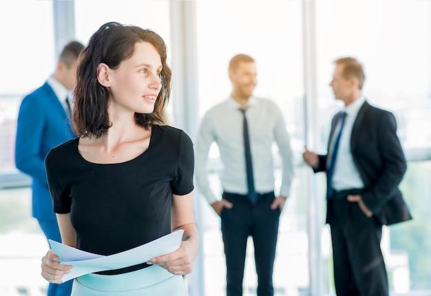 Geschäftsfrau mit den dokumenten, die weg schauen