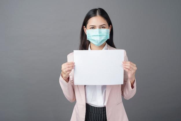Geschäftsfrau mit der chirurgischen maske hält leeres papier