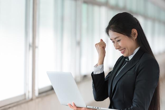 Geschäftsfrau mit der großen jobgeste, die laptop betrachtet.