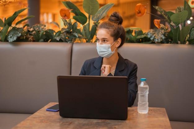 Geschäftsfrau mit der medizinischen maske, die an ihrem laptop arbeitet