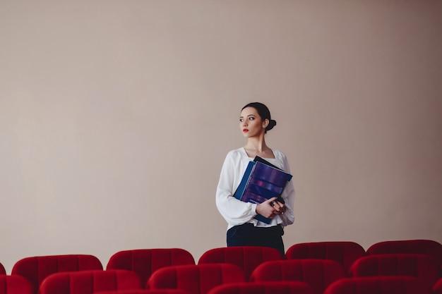 Geschäftsfrau mit dokumenten auf hintergrund der wand