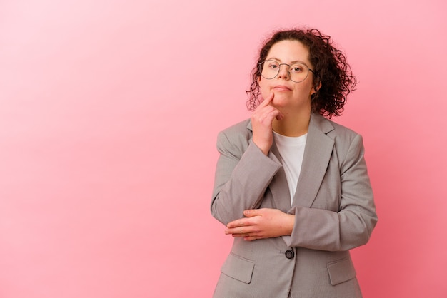 Geschäftsfrau mit down-syndrom lokalisiert auf rosa wand entspanntes denken über etwas, das einen kopienraum betrachtet.
