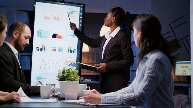 Geschäftsfrau mit dunkler haut, die finanzdiagramme mit präsentationsmonitor erklärt