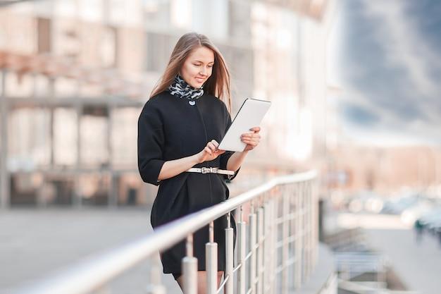 Geschäftsfrau mit einem digitalen tablet, stehend in der nähe des geschäftszentrums