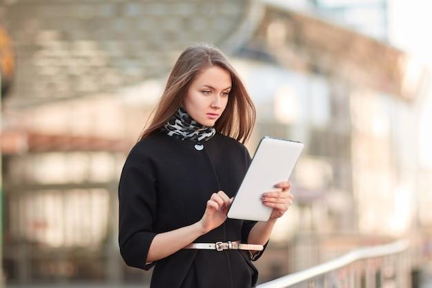 Geschäftsfrau mit einem digitalen tablett, das nahe dem geschäftszentrum steht