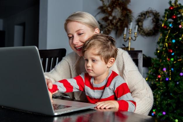 Geschäftsfrau mit einem kind arbeitet mit laptop zu hause büro während der pandemie