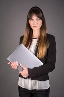 Geschäftsfrau mit einem laptop auf einem grauen hintergrund